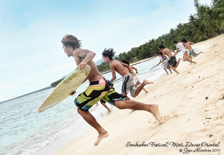 Skimboarders rush for the waves by Jojie Alcantara