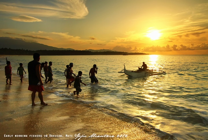 Fisherfolks at sunrise in Dahican by Jojie Alcantara